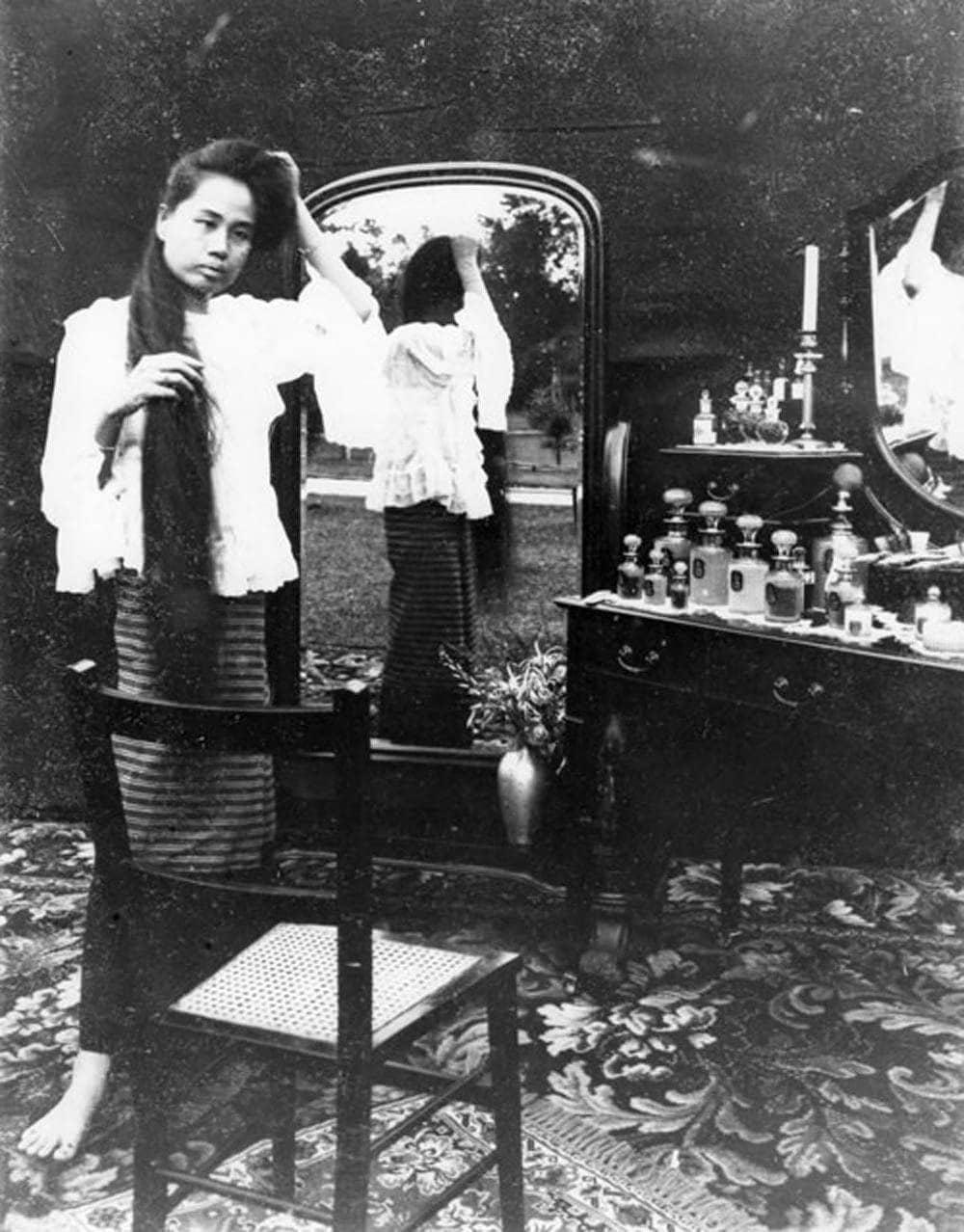 Dara Rasamee unwinding her hair before the full-length mirror. c1902.